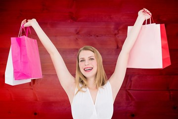 Composite image of young woman holding up shopping bags