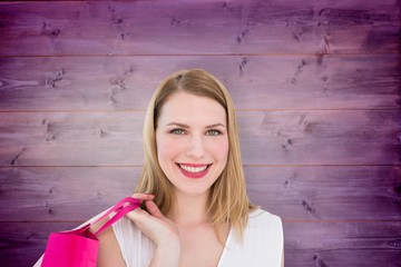 Portrait of a smiling blonde woman holding shopping bags