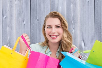 Petty woman smiling at the camera with shopping bags