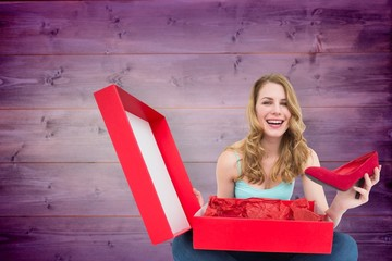Composite image of smiling young woman showing her new shoes