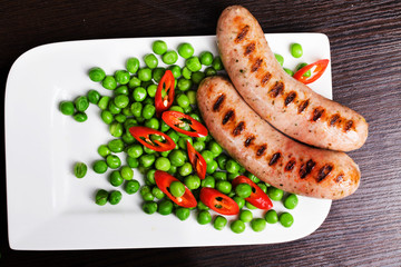 Grilled sausages with easy side dish of green peas, chili