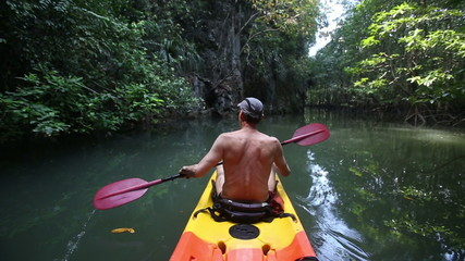 elder bare trunk man is rowing in canoe past a cliff and mangrov