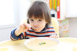 Child eating vegetable cream soup. Healthy nutrition