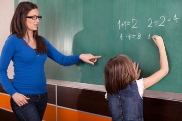 Little girl in primary school writing mathematics on chalkboard