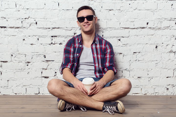 Young charming hipster sitting against the wall smiling with