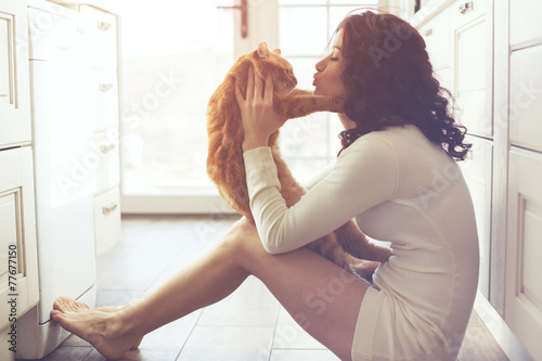Girl playing with cat - 77677150