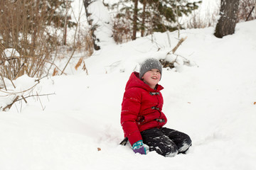 A boy sliding down a hill in snowy landscape