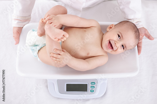Measuring smiling beautiful comfortable little baby - 77677990