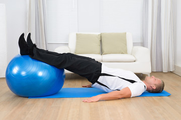 Man Exercising On A Pilates Ball