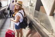Leinwanddruck Bild - Young girl with the suitcase standing on the escalator. Travel