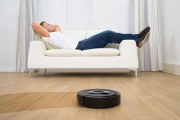Robotic Vacuum Cleaner In Front Of Man Relaxing