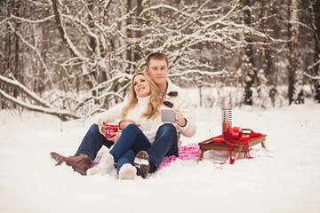 romantic couple relaxing in the winter forest and drinking tea