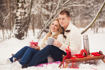 Happy couple in white sweater sitting with knitted tea cups