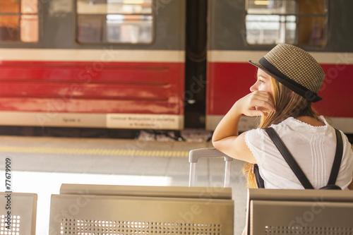 Leinwanddruck Bild Girl waiting for the train at the railway station. Travel..