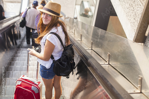 Young girl with the suitcase standing on the escalator. Travel - 77679929