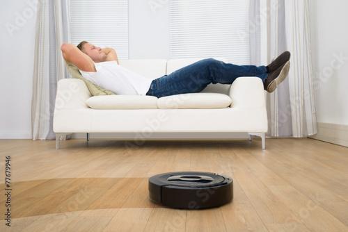 Leinwanddruck Bild Robotic Vacuum Cleaner In Front Of Man Relaxing