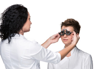 Optometrist holding an eye test glasses and giving to young