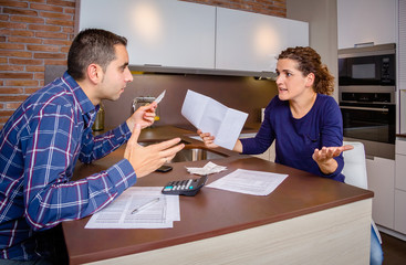 Angry young couple arguing by credit card debts