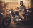 Man and vintage style cafe-racer motorcycle in garage