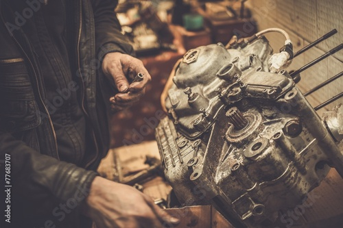 Mechanic working with with motorcycle engine in a workshop - 77683707