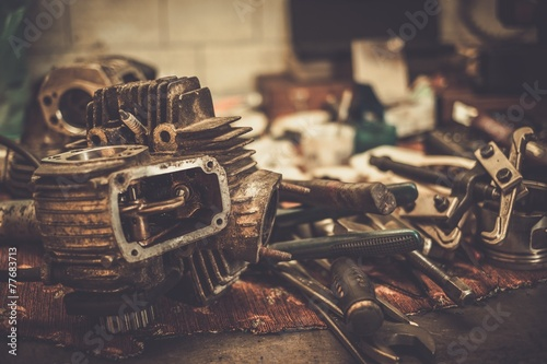Part of motorcycle engine on a table in workshop - 77683713