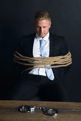 Businessman Tied With Rope Sitting In Front Of Table
