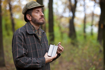Man with beard opens the flask in autumn forest