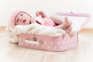 Neugeborenes Baby fühlt sich wohl auf einer Decke im rosa Koffer