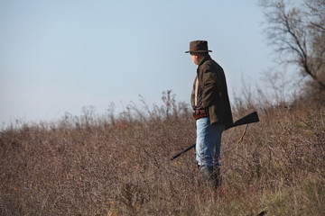 Hunter with a gun on steppe slope