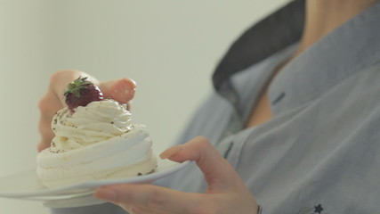 Seductive girl eating cream with fingers from cake while