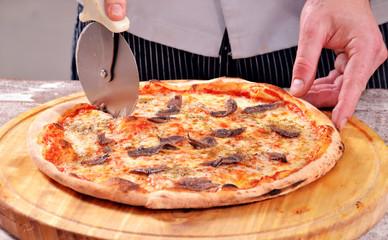 Cocinero cortando pizza napoli,preparando pizza.