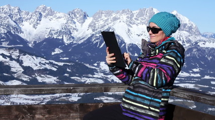 Young woman is using a tablet pc in the mountains, Alps