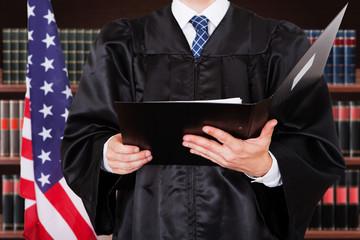 Close-up Of Male Judge Holding Folder