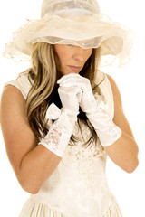 woman in a white dress and hat gloves hands under chin