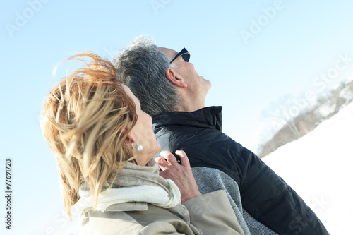 Portrait of happy senior couple in winter season - 77691728