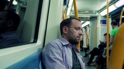 Young man sleeping on metro train