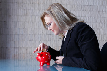 Blonde businesswoman put coins into piggy bank