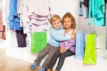 Boy and girl sit hugging under hangers in shop
