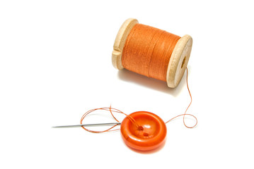 orange spool of thread, and button