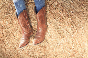 Western style image of cowgirl's legs in jeans and boots on