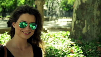 Portrait of young happy attractive woman in city park