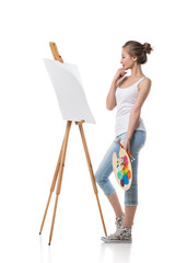 Thoughtful girl standing by canvas.