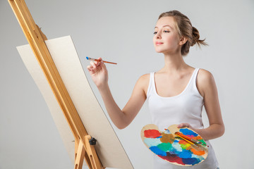 Girl paints on canvas with oil colors over white
