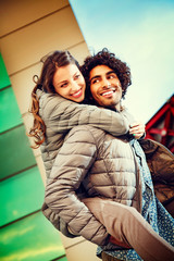 Man Giving Piggy Back Ride to Woman Outdoors