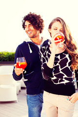 Happy vivacious couple drinking cocktails