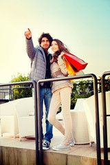 Young couple standing pointing ahead