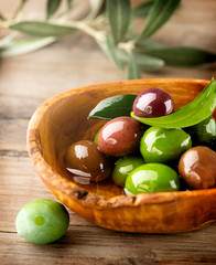 Olives and Olive Oil on the wooden table. Vertical image