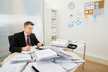 Businessman With Heap Of Folders On Desk