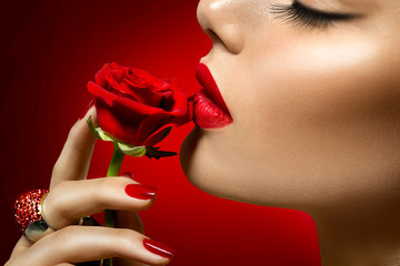 Beautiful model woman kissing red rose flower