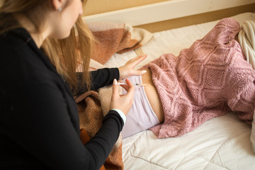 woman doing injection in girls bottom lying on bed
